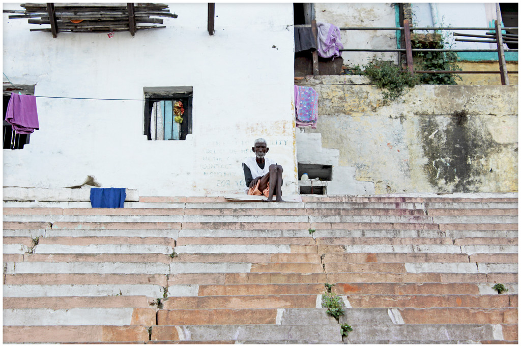 Man sitting on the steps next to the river Ganga.
